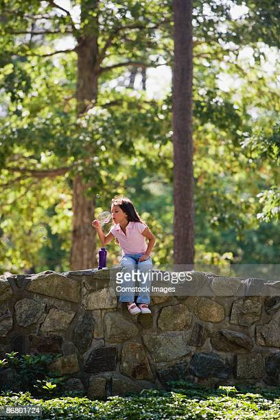 Girl playing with bubbles outdoors