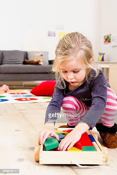 Girl playing with building blocks at home
