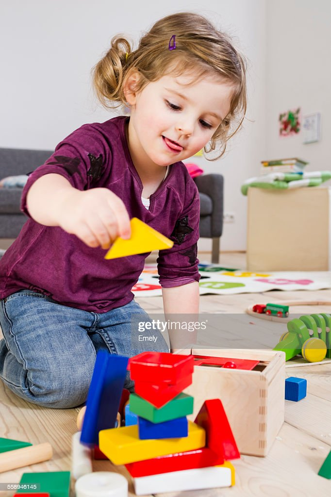 Girl playing with building blocks at home : Stock Photo