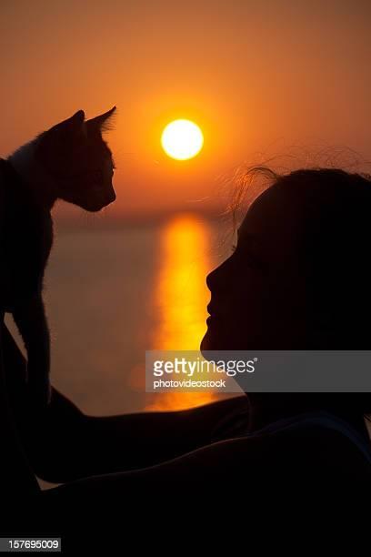 Fille jouant avec un chat contre coucher de soleil saisissant