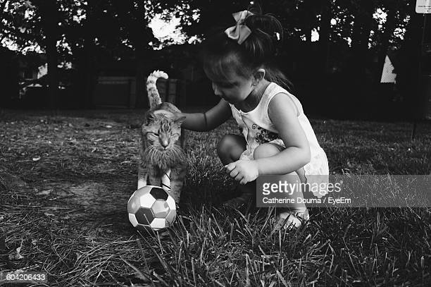 Girl Playing With Cat And Ball On Field In Back Yard