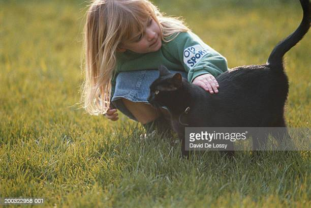 Girl (2-3) playing with cat in garden