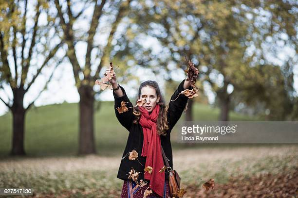 girl playing with colourful leaves at fall