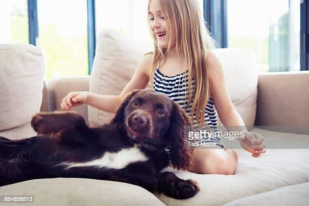 Girl playing with dog lying down on sofa at home