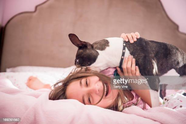 Girl playing with dog on bed