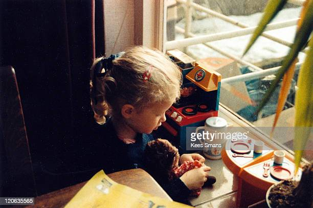girl playing with doll and toy kitchen - puppe stock-fotos und bilder