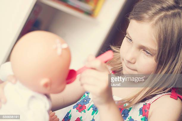 Girl (6-7) playing with doll
