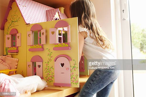 girl playing with dollhouse in bedroom - dollhouse stock pictures, royalty-free photos & images