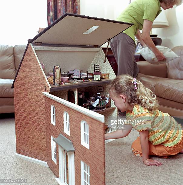 Girl (4-6) playing with dolls house, mother in background