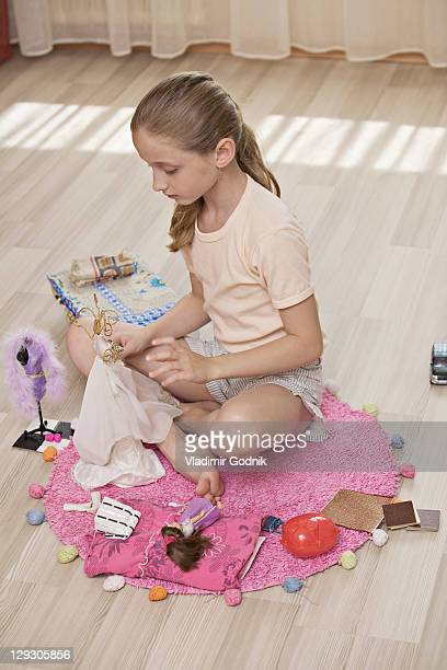 A girl playing with dolls