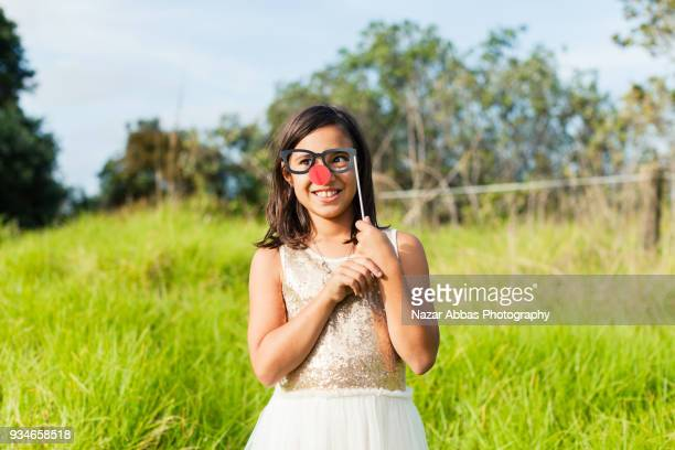 Girl playing with eyeglasses props outdoor.