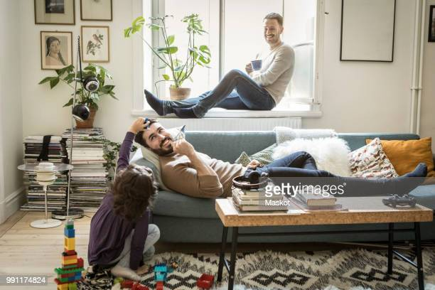 girl playing with fathers while man sitting on window sill in living room - union gay fotografías e imágenes de stock