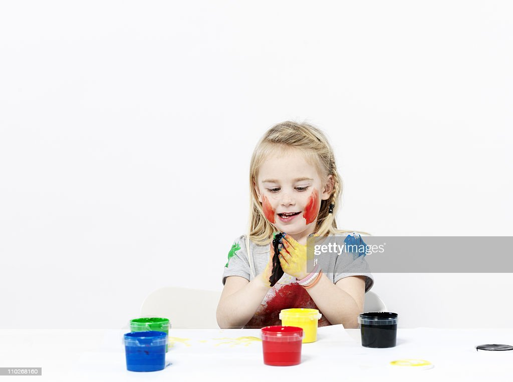 Girl playing with finger paint : Stock Photo
