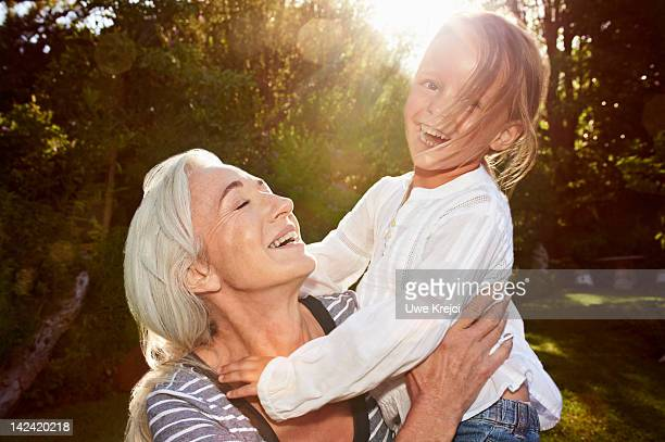 Girl playing with grandmother in the garden