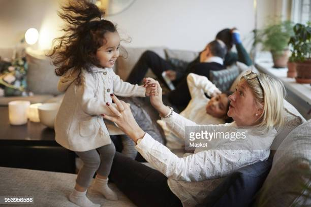girl playing with grandmother on sofa by family at home - family at home stock photos and pictures