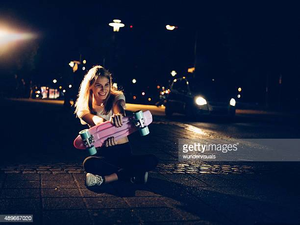 Girl playing with her skateboard on city sidewalk at night