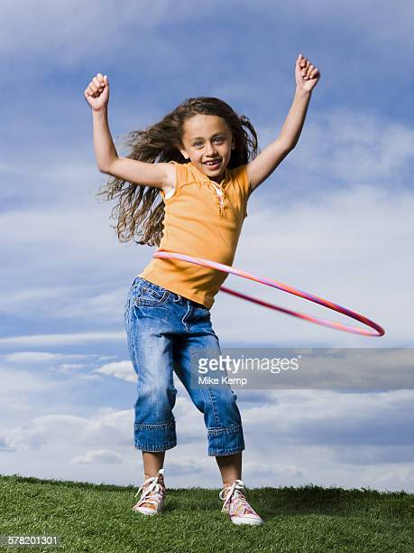 Girl playing with hula hoop outdoors