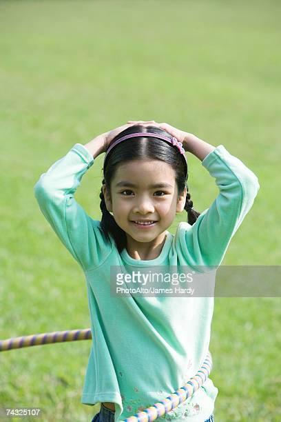 Girl playing with hula hoop, smiling at camera