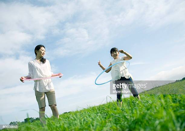 Girl playing with Hula-Hoop in field with mother