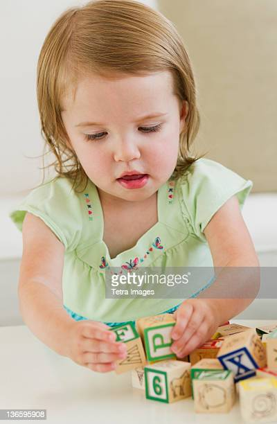 Girl (2-3) playing with letter blocks