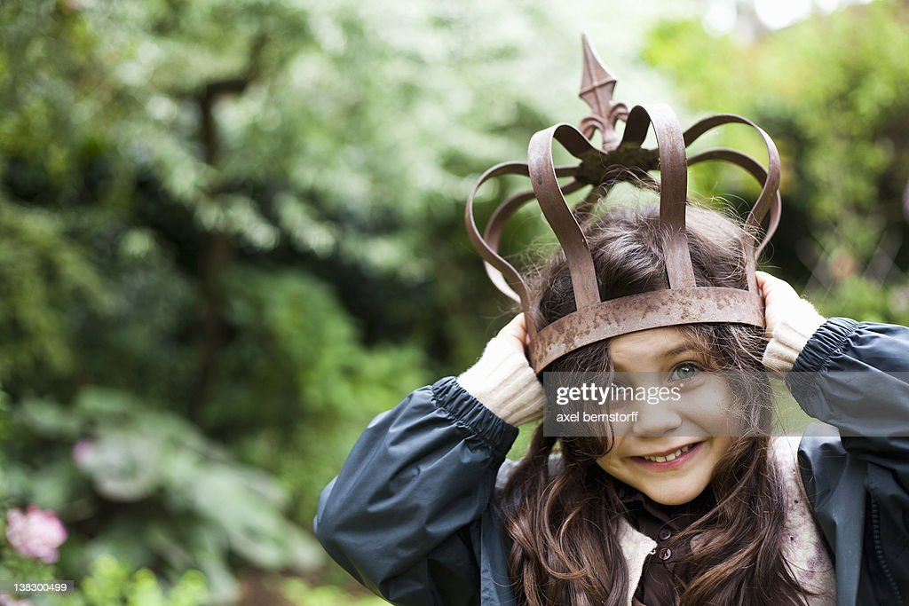 Girl playing with metal crown outdoors : Stock Photo