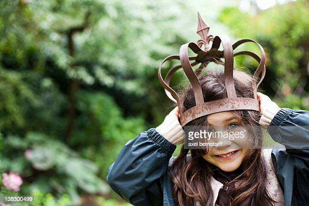 Girl playing with metal crown outdoors