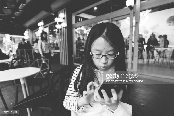 girl playing with mobile phone in the arcade. - myopia stock photos and pictures