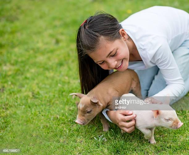 Niña jugando con cerdos