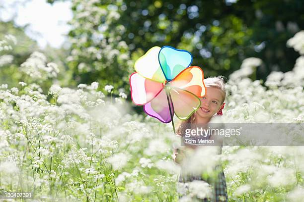 Mädchen spielen mit Windrad in Feld mit Blumen