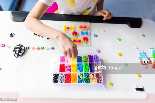 Girl playing with plastic bead.