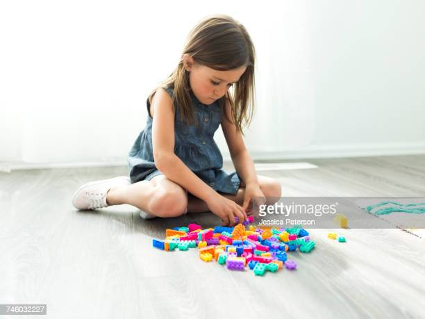 girl (6-7) playing with plastic blocks - denim dress stock photos and pictures