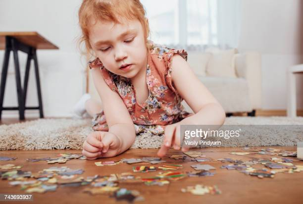girl playing with puzzle pieces while lying on carpet at home - puzzle stock-fotos und bilder