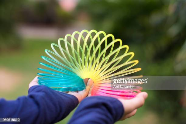 girl playing with rainbow colored wire spiral toy on white background. - flexibility stock pictures, royalty-free photos & images