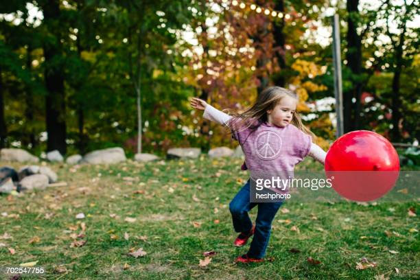 girl playing with red balloon in garden - heshphoto stock pictures, royalty-free photos & images