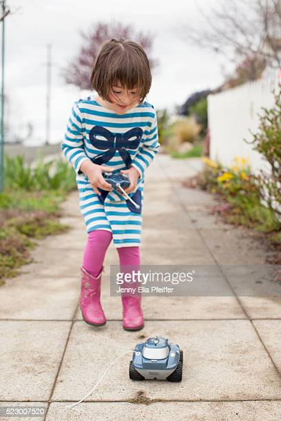 girl (4-5) playing with remote control car - remote control car games stock pictures, royalty-free photos & images