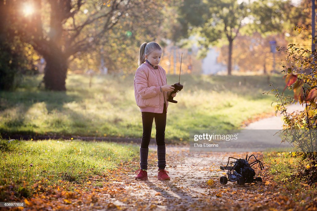 Girl playing with remote control toy outdoors : Stock Photo