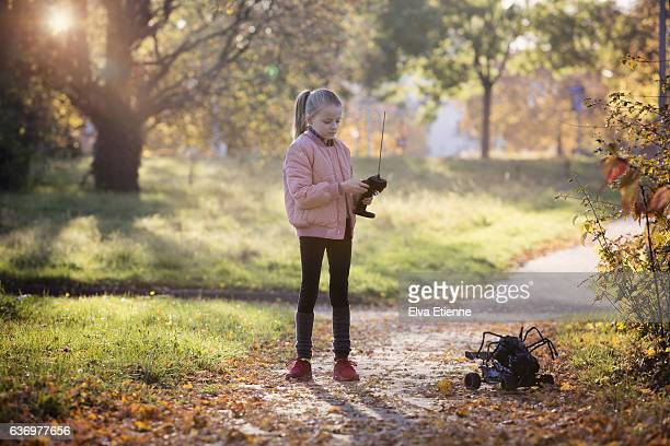 Girl playing with remote control toy outdoors