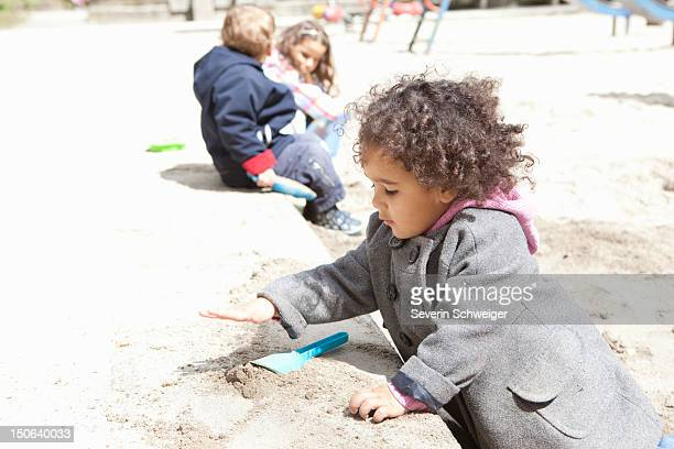 Girl playing with sand in playground