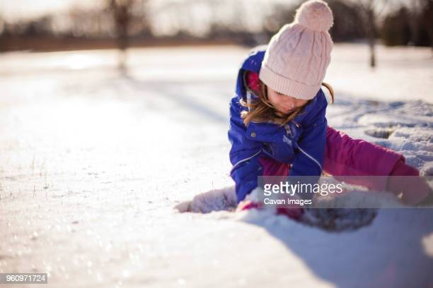 Girl playing with snow on sunny day