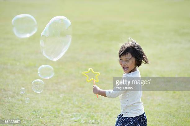 Girl playing with soap bubbles in green