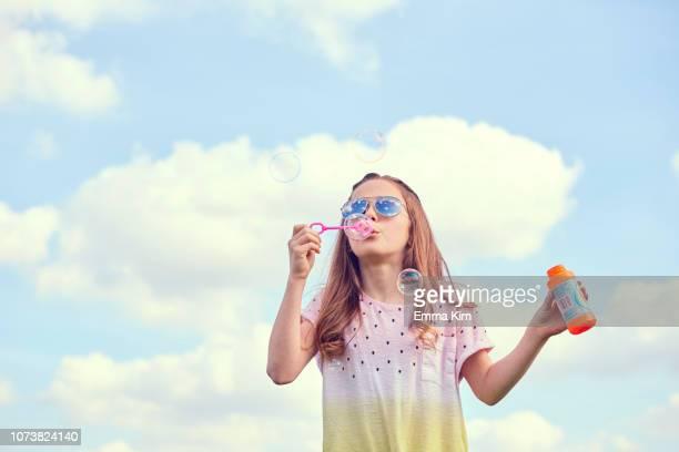 girl playing with soap bubbles - só uma menina - fotografias e filmes do acervo