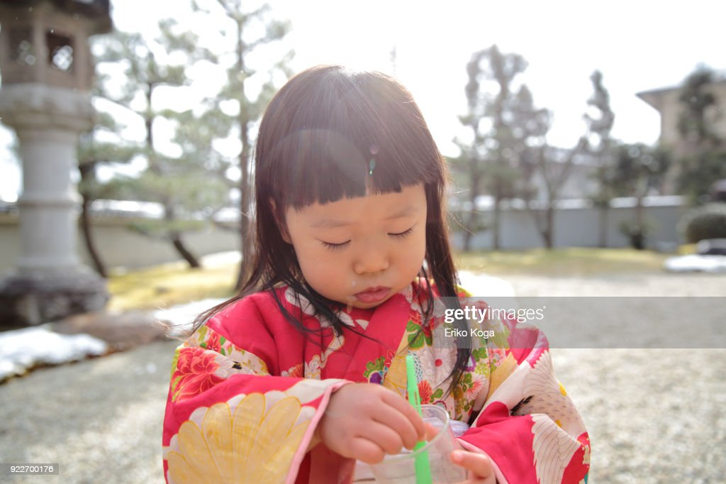 2 years and one month old girl in kimono playing with soap bubbles in garden in Kyoto.