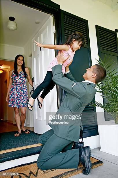 Girl playing with soldier father at door