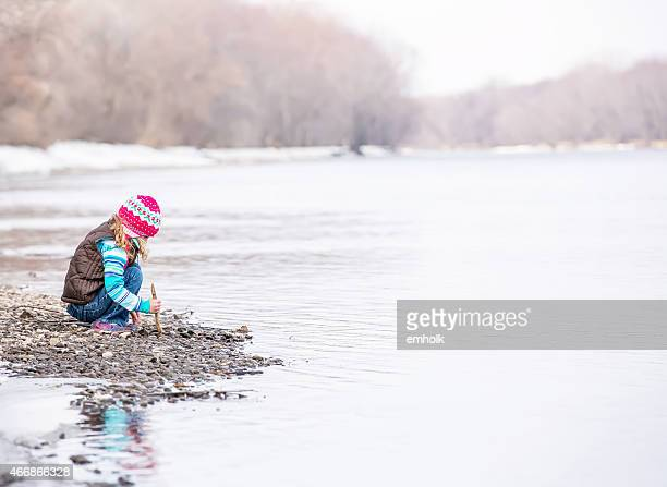 Girl Playing With Stick By River in Early Spring