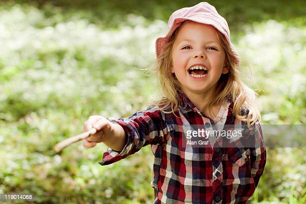 Girl playing with stick outdoors
