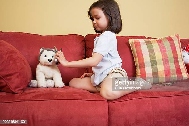 girl (5-7) playing with stuffed animal on sofa - dead girl foto e immagini stock
