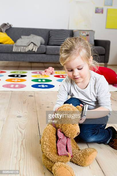 Girl playing with teddy bear at home