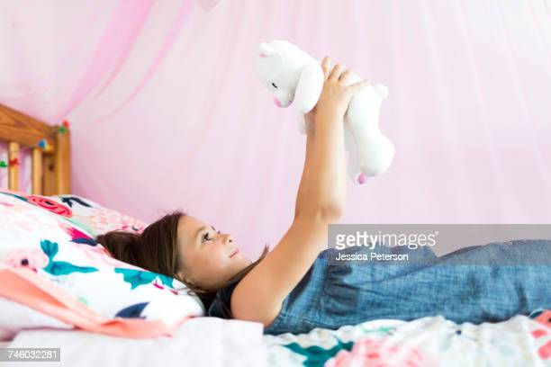 Girl (6-7) playing with teddy bear in bedroom