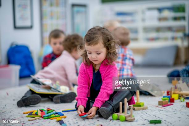 girl playing with tiles - preschool student stock pictures, royalty-free photos & images