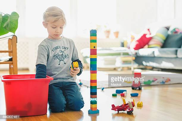 Girl playing with toy blocks while kneeling on floor at home